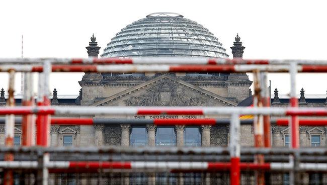 Foto: Das Reichstagsgebäude hinter Absperrgittern vor grauem Himmel